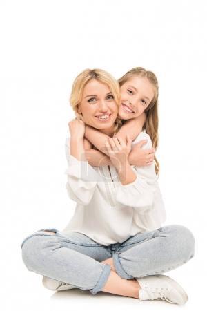 Photo pour Fille heureuse embrassant jeune mère isolée sur blanc - image libre de droit