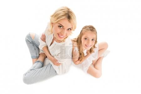 Photo for Overhead view of smiling mother and preteen daughter looking at camera isolated on white - Royalty Free Image