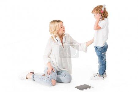 Photo pour Petit garçon dans les écouteurs des conversation avec mère isolée sur blanc - image libre de droit