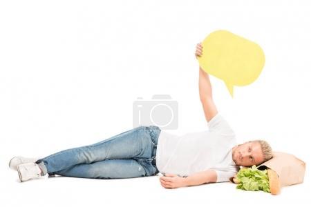 Photo pour Homme avec bannière vierge à la main couché sur un sac en papier avec de la nourriture isolée sur blanc - image libre de droit