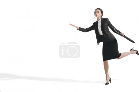 businesswoman running and holding umbrella
