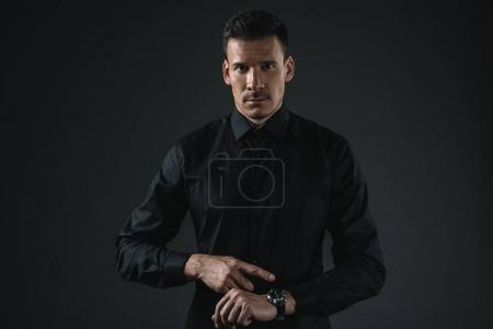 Photo for Serious fashionable man in black outfit pointing on watch, isolated on grey - Royalty Free Image