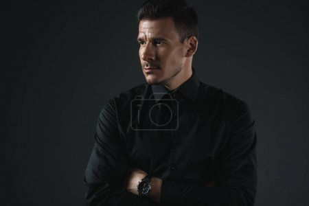 Photo for Fashionable man in black outfit with crossed arms looking away, isolated on grey - Royalty Free Image