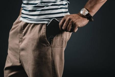 man putting smartphone into pocket