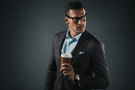 Photo for Portrait of stylish man with coffee to go in hand looking away isolated on grey - Royalty Free Image