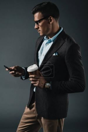 Photo for Side view of businessman drinking coffee to go in hand and using smartphone isolated on grey - Royalty Free Image