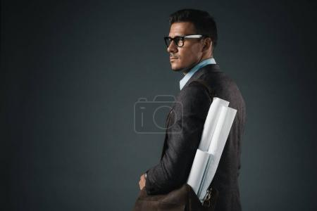 businessman with blueprints in bag looking away