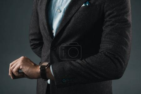 Stylish man looking at hand watches