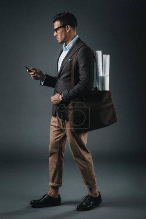 Foto de Joven empresario guapo con planos en el bolso con smartphone - Imagen libre de derechos