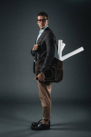 Foto de Joven hombre de negocios caucásico con planos en bolsa mirando lejos - Imagen libre de derechos