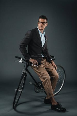 Photo pour Jeune homme d'affaires élégant assis sur le vélo et regardant loin - image libre de droit