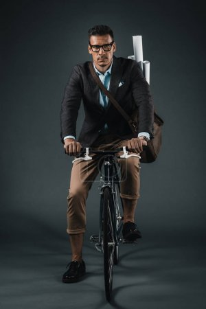 confident businessman with bag riding on bicycle