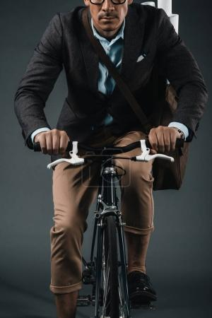 young businessman with bag riding on bicycle