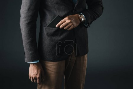 1 man putting smartphone in pocket of blazer