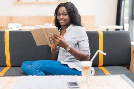 Photo pour Belle africaine américaine livre de lecture tout en étant assis dans le café - image libre de droit