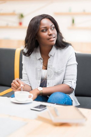 Photo for African american woman having coffee break and looking away in cafe - Royalty Free Image