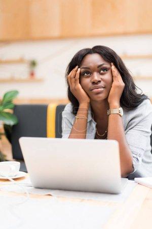 Photo pour Belle femme africaine américaine réfléchie utilisant un ordinateur portable dans un café - image libre de droit