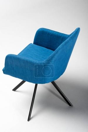 Photo for Studio shot of stylish chair with blue fabric top and triangular metallic legs on white - Royalty Free Image