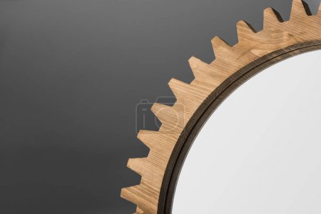 Photo for Close-up cropped view of mirror framed by wooden cogwheel on gray - Royalty Free Image