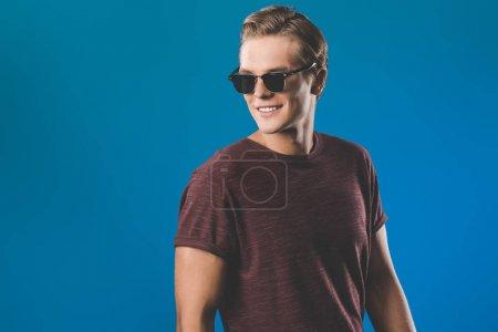 Photo pour Jeune homme souriant dans des vêtements élégants et des lunettes de soleil vintage - image libre de droit