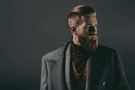 Photo for Portrait of serious handsome bearded man looking away isolated on black - Royalty Free Image