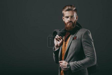 Foto de Retrato de hombre con estilo con la chaqueta en la mano mirando a cámara aislada en negro - Imagen libre de derechos