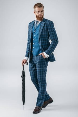 Photo for Fashionable young man with hand in pocket holding umbrella isolated on grey - Royalty Free Image