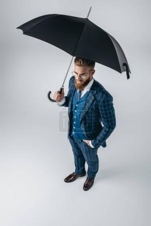 Photo for High angle view of handsome man in suit with opened umbrella isolated on grey - Royalty Free Image