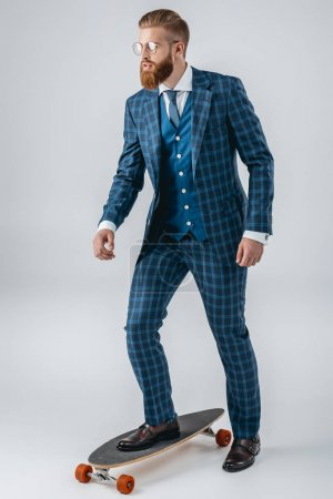fashionable man in suit on skateboard