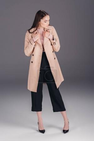 Photo pour Songeur à la mode jeune femme en manteau isolé sur fond gris - image libre de droit