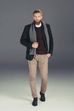 Photo pour Homme élégant avec écharpe en regardant la caméra isolée sur fond gris veste - image libre de droit