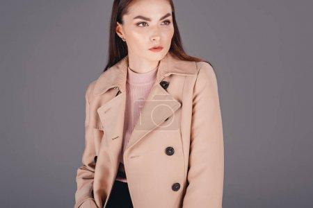 Photo pour Portrait de jeune femme à la mode manteau à la recherche de suite isolé sur fond gris - image libre de droit