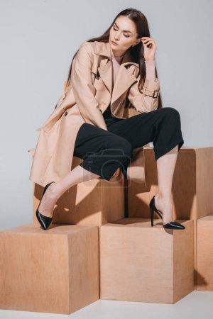 Modische Frau sitzt auf Holzklötzen