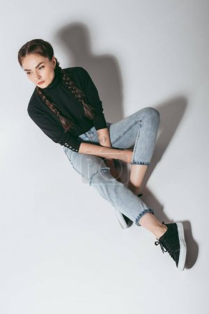 Photo for Stylish young woman looking away while sitting on floor - Royalty Free Image