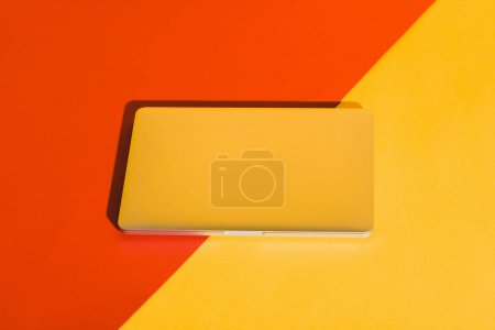 Photo for Stylish closed laptop on yellow and red background - Royalty Free Image