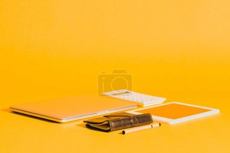 Photo for Laptop, digital tablet, diary and calculator on yellow with copy space - Royalty Free Image