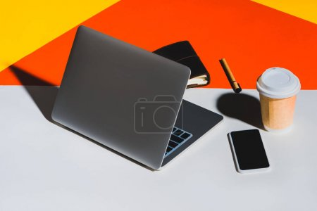 Photo for Laptop, smartphone, disposable cup of coffee and office supplies - Royalty Free Image