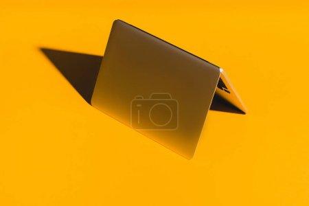 overturned laptop on yellow