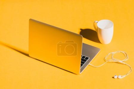 laptop, earphones and coffee cup