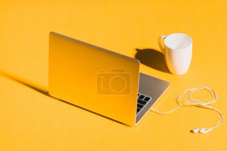 Photo for Laptop with earphones and coffee cup on yellow background - Royalty Free Image