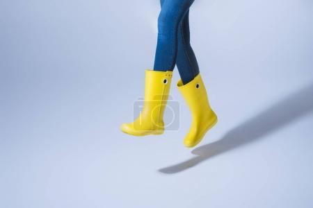 woman jumping in rubber boots