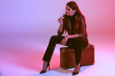 Smoking girl sitting on suitcase