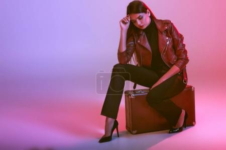 Photo for Attractive model in leather jacket sitting on suitcase, on pink - Royalty Free Image