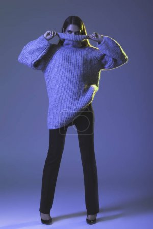 Photo for Charming beautiful girl posing in warm trendy sweater, on blue - Royalty Free Image