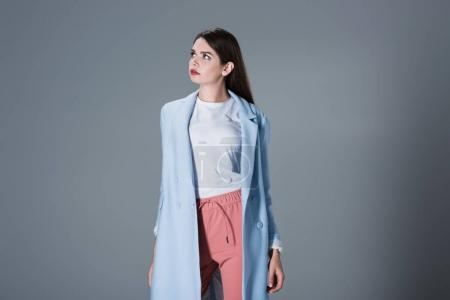 Photo for Fashionable girl posing in blue trench coat and pink trousers, on grey - Royalty Free Image