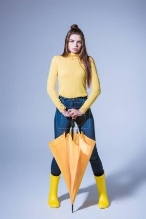 girl in rubber boots with umbrella
