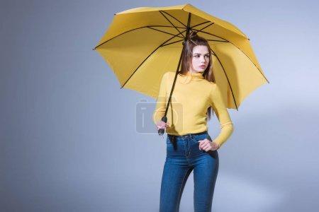 Photo pour Charmante fille posant en jeans avec parapluie jaune, isolé sur gris - image libre de droit