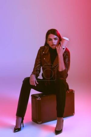 girl with coffee sitting on suitcase