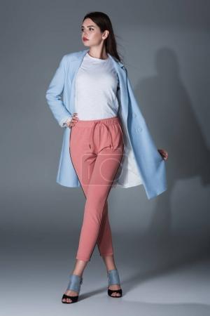 Photo pour Élégant modèle posant en Trench-Coat bleu et pantalon rose, sur fond gris - image libre de droit