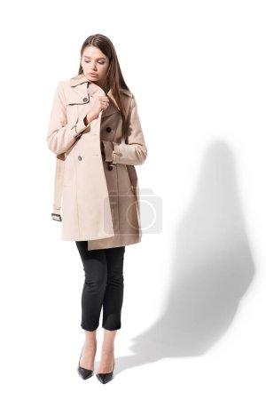 Photo pour Jolie jeune fille qui pose en Trench-Coat classique, sur blanc - image libre de droit